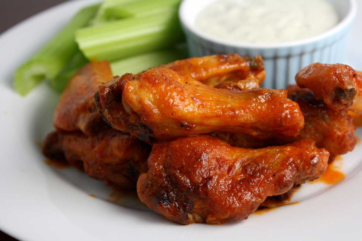 sauced wings on plate with dressing and celery